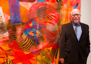 Frank Owen standing next to large artwork on wall